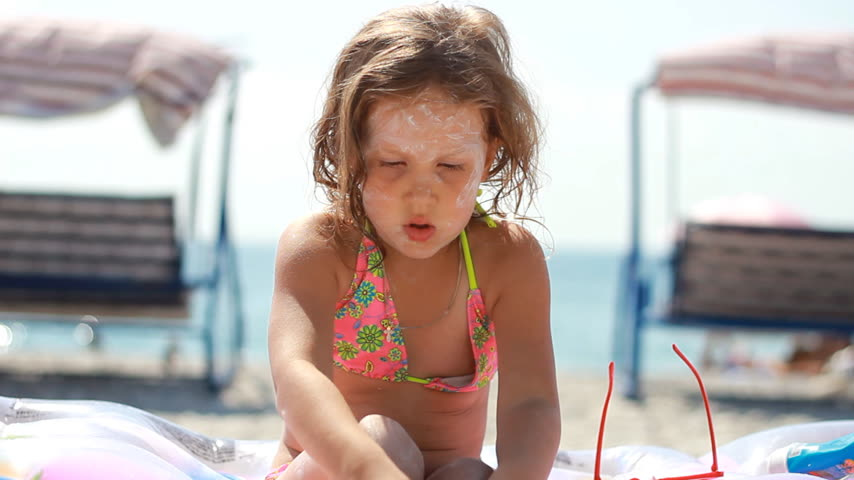 Child smearing sun cream fase and body. Sunburn. Suncream cream. Sunprotection cream. Cute baby girl in sunglasses sunbathes on a beach near the sea