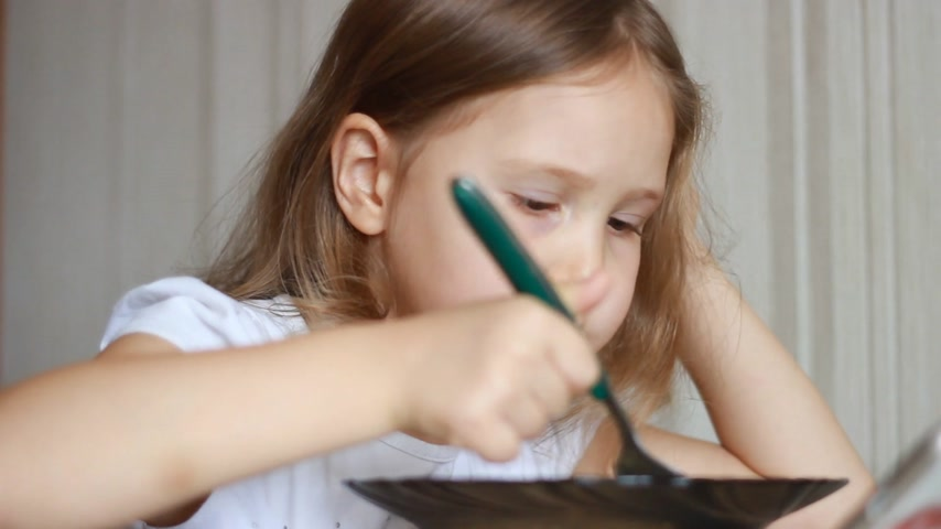apetite : Child eats soup with a spoon. Closeup baby girl sitting at the table of home cooking and eating food