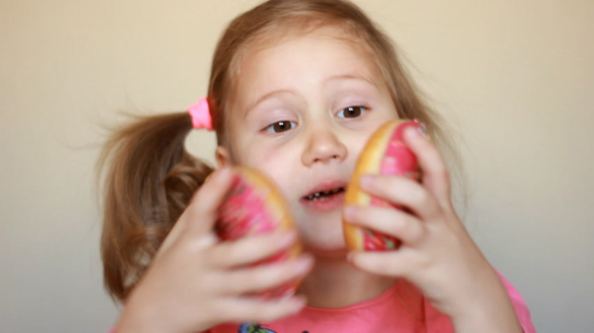 Child eats donut. Closeup baby girl eating doughnut with glase. Delicious, sweet, sweettooth