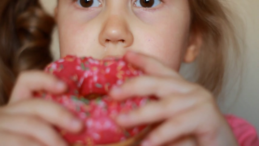 Child mouth bites rose donut. Closeup baby girl eating doughnut with glase. Delicious, sweet, sweettooth.