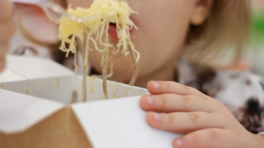 Closeup baby girl eating pasta with cheese. Child eats fastfood pasta in box Stock Footage