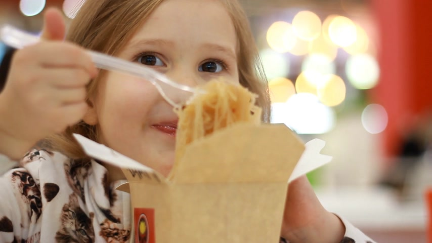 Closeup baby girl eating pasta with cheese. Child eats fastfood pasta in box Filmati Stock