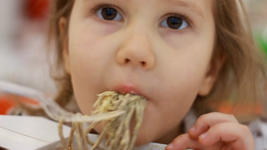 Child eating pasta with cheese. Portrait closeup baby girl eats fastfood pasta in box Stock Footage