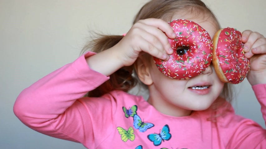 Child and donut. Closeup baby girl eating doughnut with glase. Delicious, sweet, sweettooth