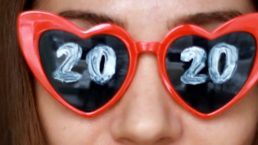 Close up portrait of a woman in sunglasses with numbers 2020. New Year. Christmas. Girl smiles and looks at the camera Filmati Stock