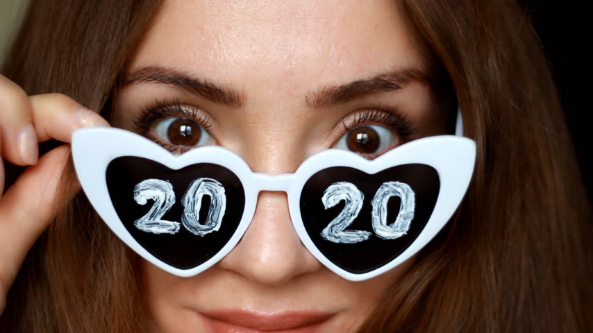 Close up portrait of a woman in sunglasses with numbers 2020. New Year. Christmas. Girl smiles and looks at the camera. Selective focus