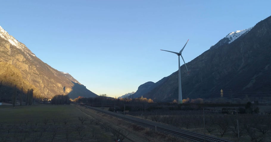 wind turbine in a montain valley with train