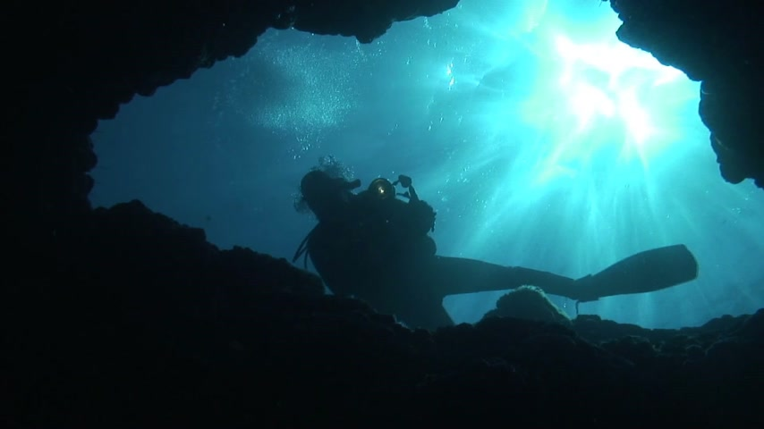barlang : Diver is exploring a cave