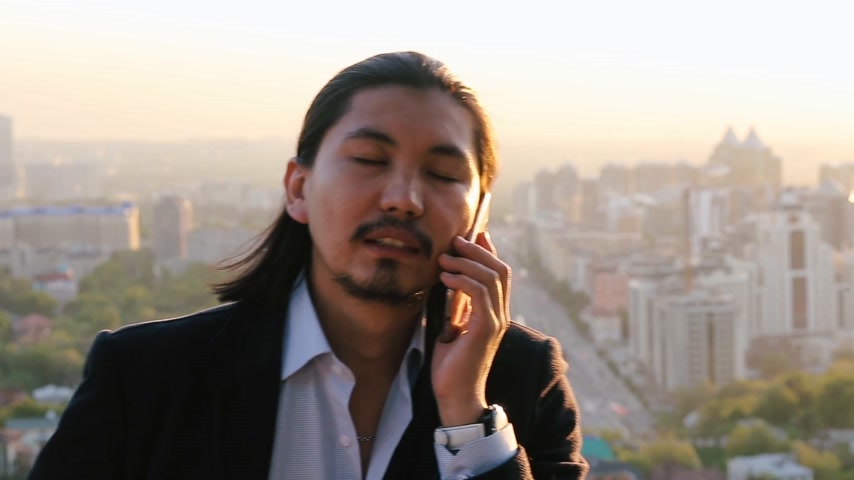 citylandscape : Professional asian businessman talking over a phone against a beautiful city background Stock Footage