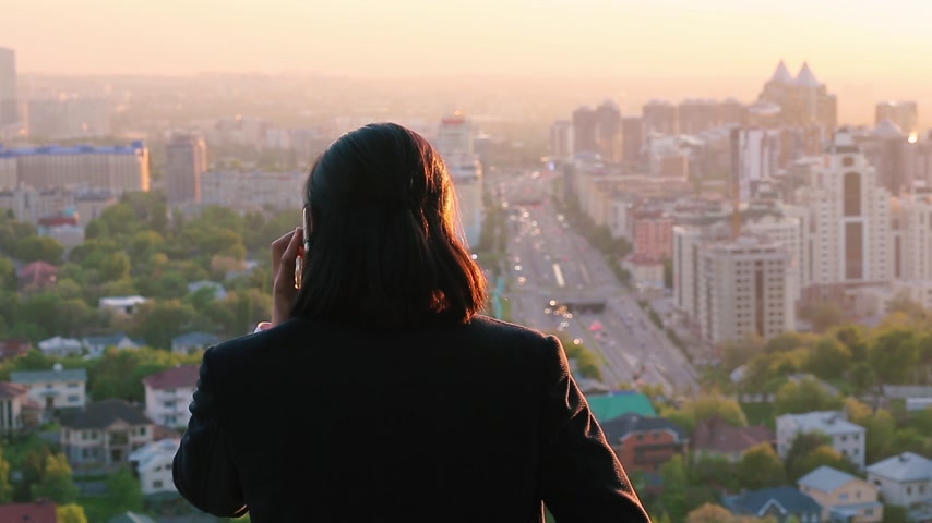 citylandscape : Wealthy businessman negotiating a deal on a phone and gazing at a marvelous city landscape Stock Footage