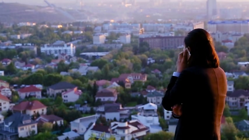 citylandscape : Wealthy enterpreneur negotiating a deal over a phone against a beautiful city background Stock Footage