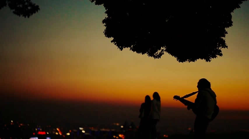 aydınlatmalı : Businessman playing and singing on a hill against a marvelous background with people taking pictures