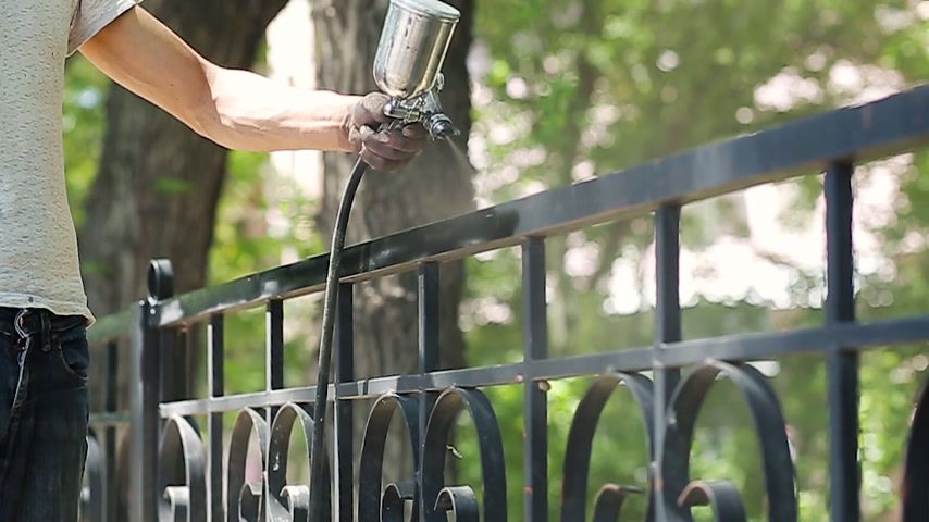 zinek : Hand spraying a black paint in slow motion on the fence in the park