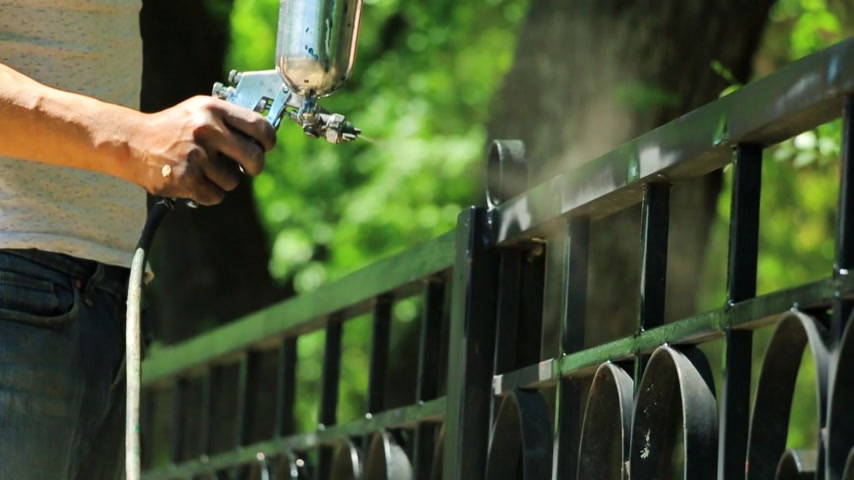 ar : Hand spraying a black paint in slow motion on the fence in the park