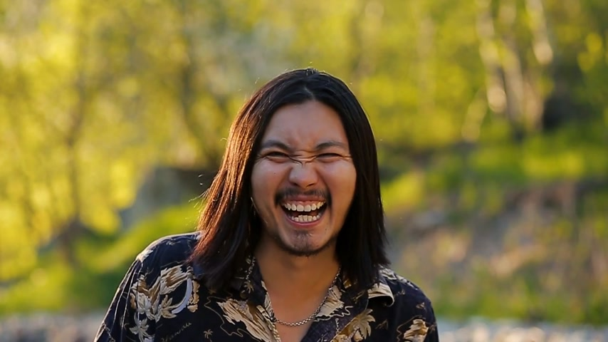menő : A long haired handsome hippy man laughing happily in the mountains against a beautiful sunset in Slow motion
