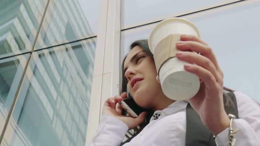 holding steady : Elegant business woman talking over a phone during a coffee break in business centre Stock Footage