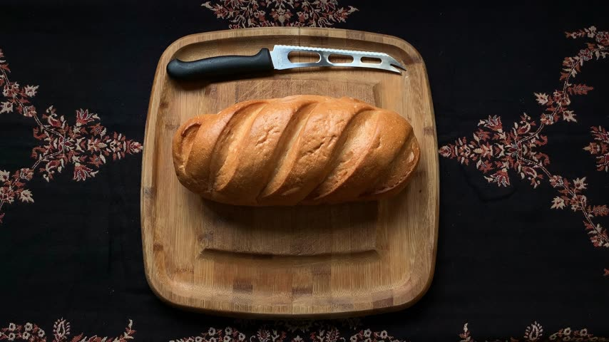 スライシング : two hands touch the bun on a wooden board