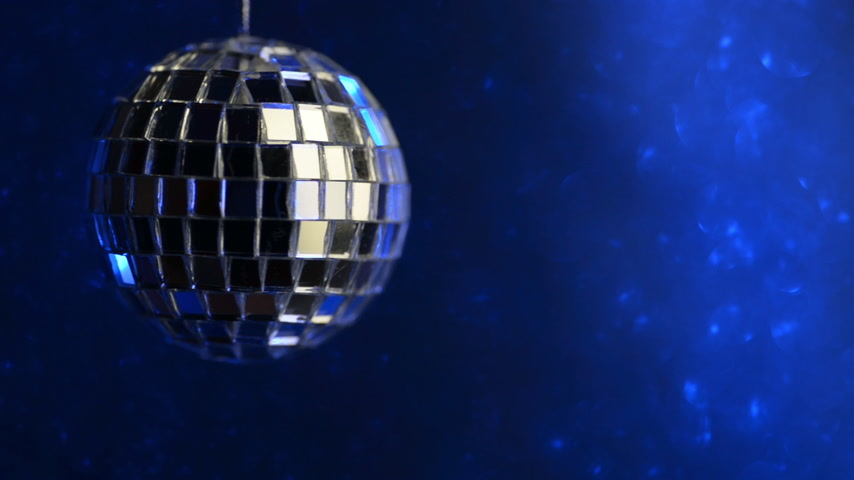 Mirror disco ball spins around. Illuminated by neon on a blue background. Stockvideo
