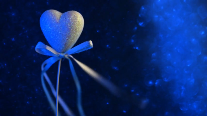 A romantic heart with sequins against a blue bokeh background. The bows are fluttering in the wind