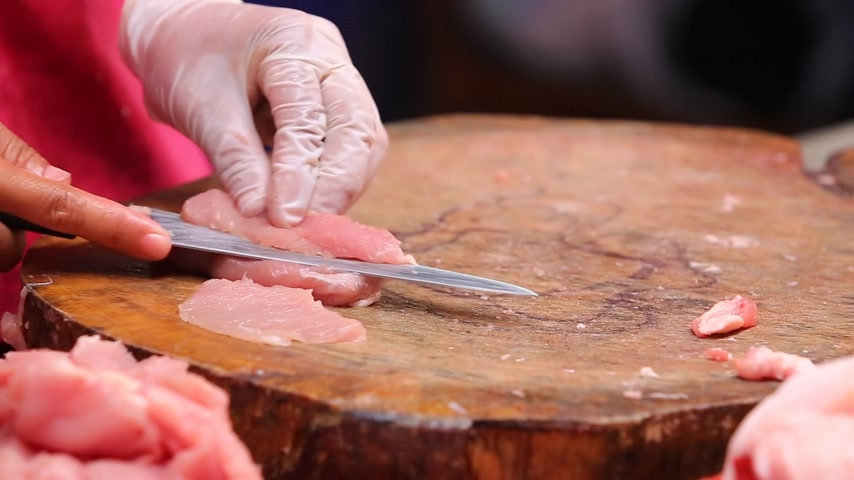 šunka : A cook slicing pork on wooden chopping block