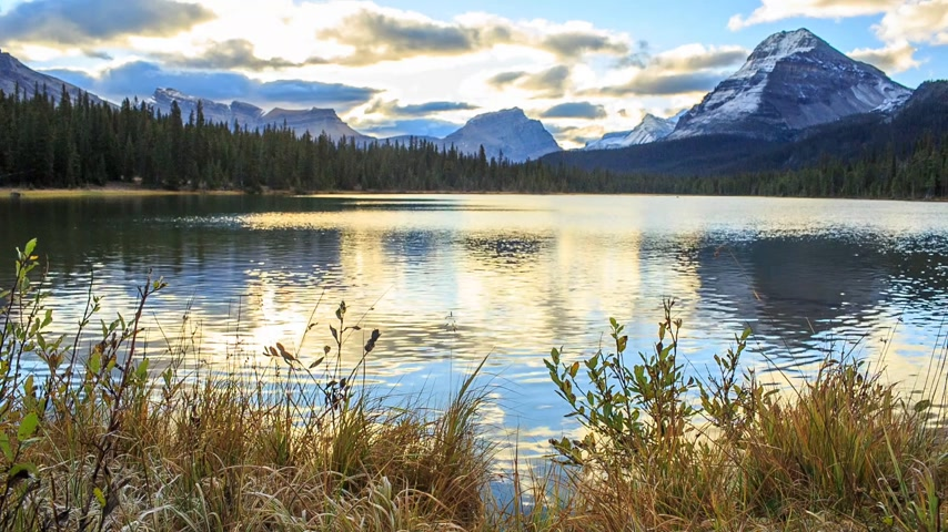 peak : Sunset on the quiet and picturesque lake. In the foreground of dry grass in the distance the peaks of the mountains reflected in the lake. RAW video.