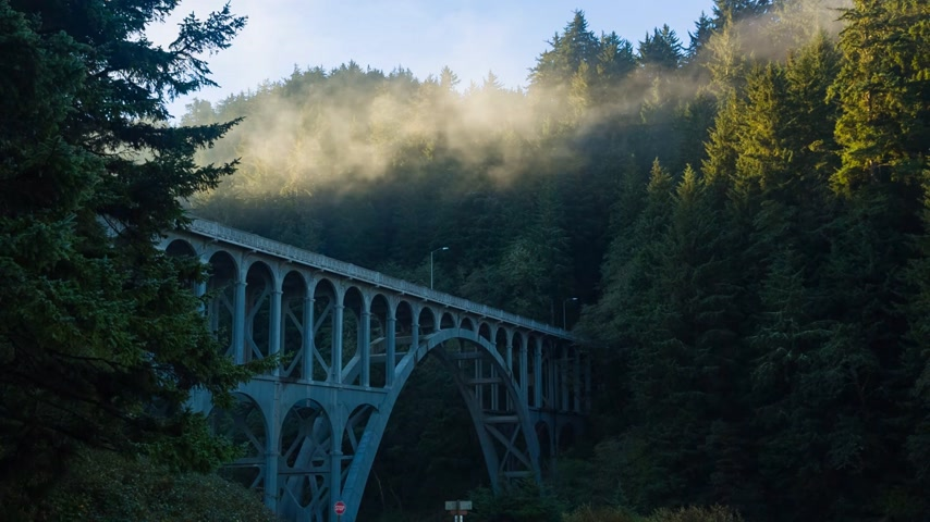 çinko : Sunlight at morning fog at Cape Creek Bridge, at the heart of Heceta Head Lighthouse Scenic Viewpoint, is the first bridge in the world to have zinc thermal sprayed over the entire structure Stok Video