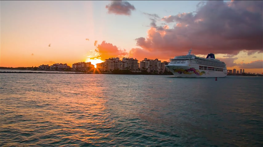 vonal : A cruise liner leaving from the port of Miami into the ocean at sunset
