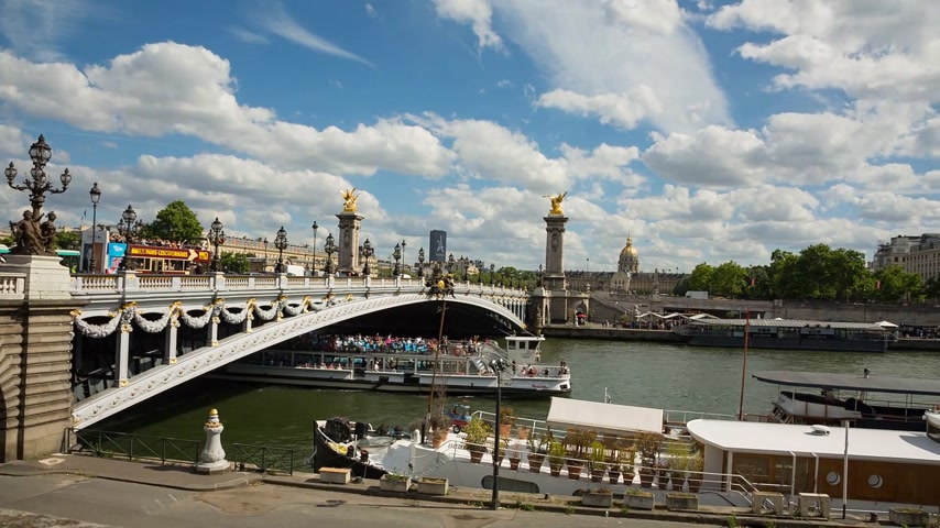 gyalogút : Paris, France - JUNE 09, 2017: A ship passing Alexander III bridge at daytime. Left to right panning. Stock mozgókép
