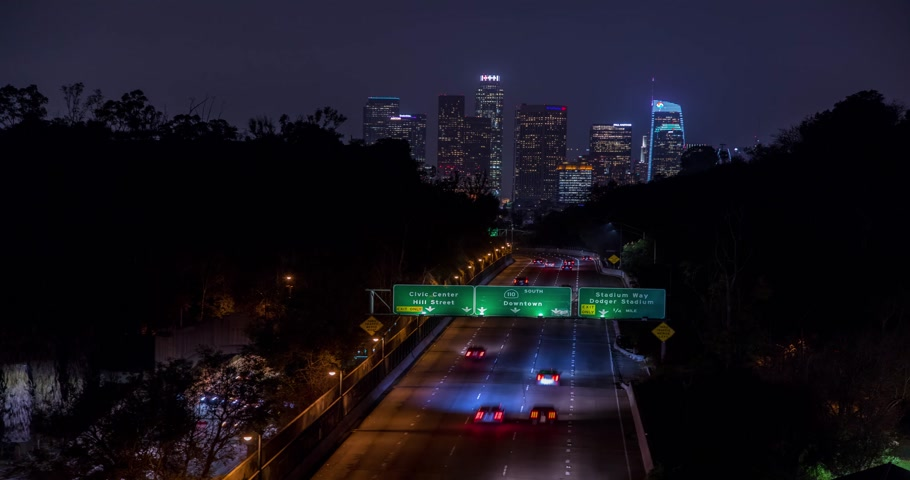 Beautiful view of Los Angeles Skyline from 110 Freeway at dusk. Close up. Traffic passing by. Timelapse with zoom effect. California, United States. Stok Video