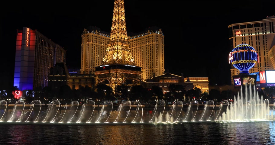 bellagio : LAS VEGAS, NEVADA - JANUARY 03, 2018: Bellagio fountain at night with a Paris hotel and Planet Hollywood hotel view on background during fountain show