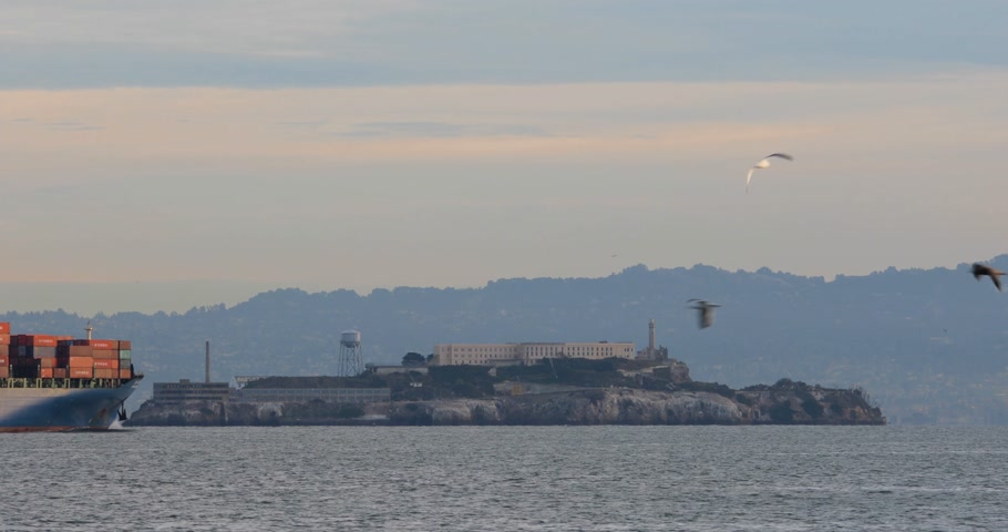 museum : SAN FRANCISCO - DECEMBER 24, 2017: A big ship passing Alcatraz Island at San Francisco bay before sunrise