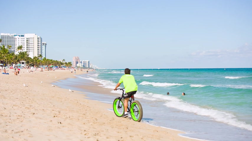 A man riding a bike on Fort Lauderdale beach
