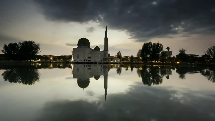 ислам : Moving cloudy clouds at sunrise scene over the mosque and reflection at the lake garden