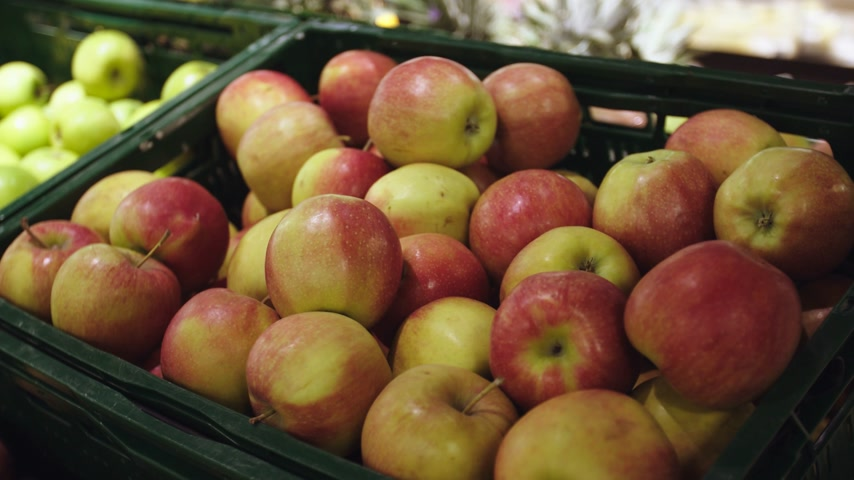 Fresh apples in store. Close up of womans hand picking up apple at market. Handheld.