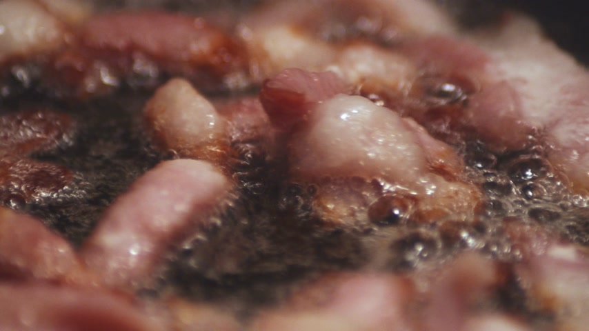 picado : Macro panning shot of chopped bacon roasting cooking on pan in oil. Stock Footage