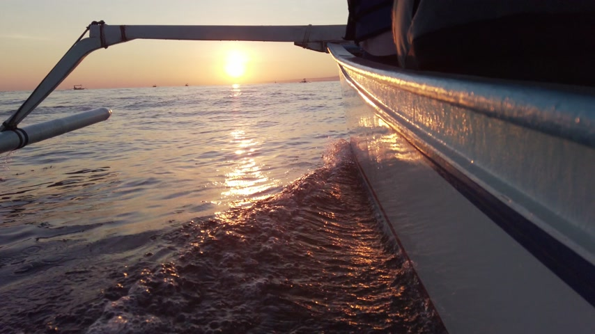 View over the side of moving boat with waves towards sunset in the open ocean.