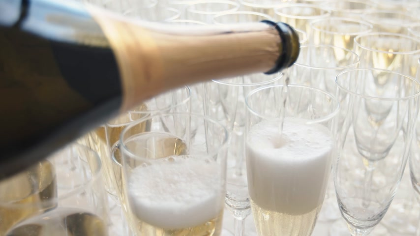 Pouring champagne from bottle into a glass slowly filling it, with many other glasses standing on the table.