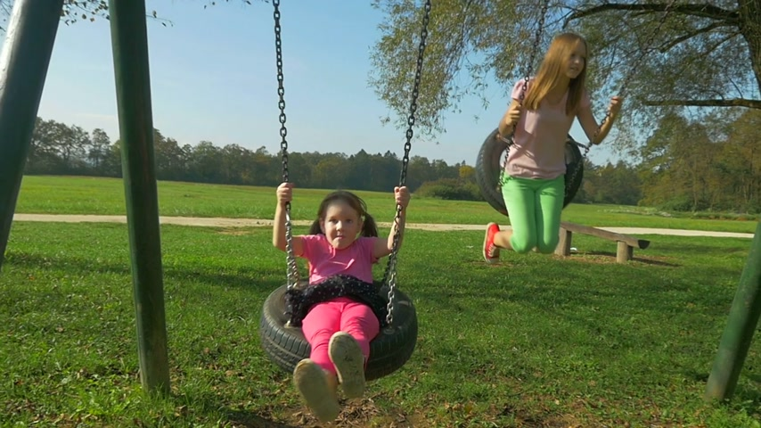 swing : Cheerful little girl and bigger sister swings, smile and enjoy the ride on playground. Stock Footage