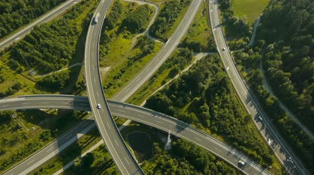 junção : Close, rear aerial view of traffic on motorway junction. Late afternoon, summertime.