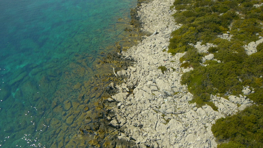 shoreline : Close, camera front, aerial perspective of sea water with some sun reflecion??, rocky coasts and bushes in summer sunny day.