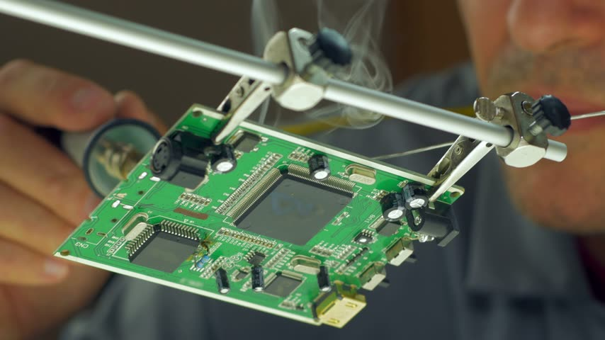 solder : 4K macro tilt up view how technician solder and try to repair a circuit board