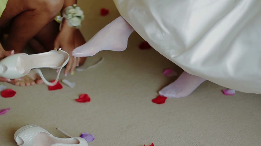 nogi : Bridesmaid Helping to Bride Put on Her Shoes