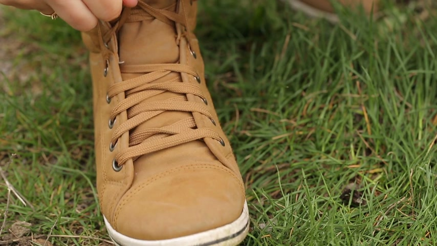 tying : Woman Tying a Shoe