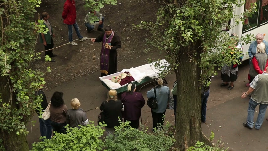 trumna : DONETSK, UKRAINE- 10 July 2014: Priest Says a Prayer Over the Dead