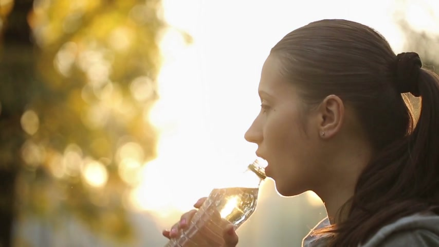 ital : Woman Drinking Water Against Sunbeams