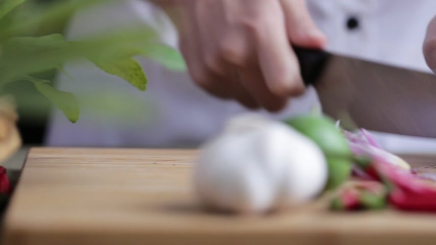 soğancık : A female hand slicing shallot on bamboo wooden plate with other Thai herbs beside.