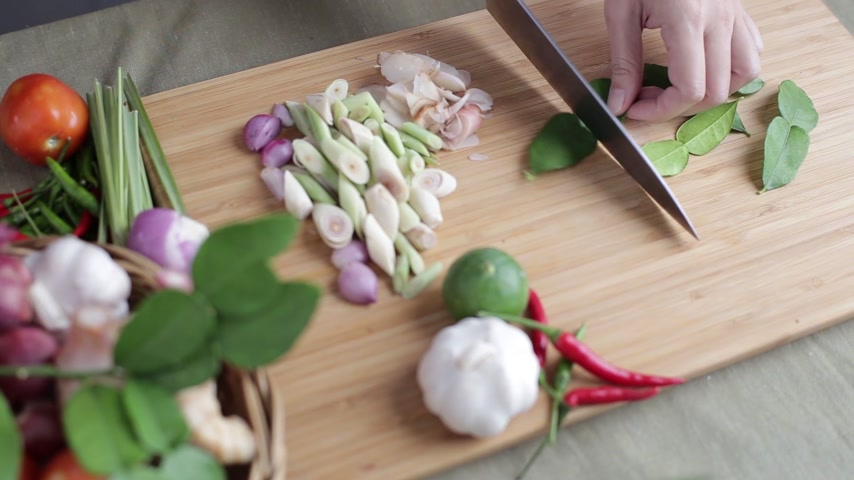 Female hand cut kaffir lime leaves in piece on bamboo wooden plate with other Thai herbs beside for Tom Yum recipe. Vídeos