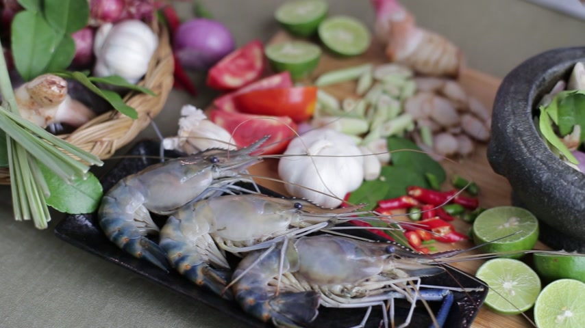 kari : Female hand pounding Thai herb in the mortar to make Tom Yum Kung with all spices and prawns beside on the chopping board.
