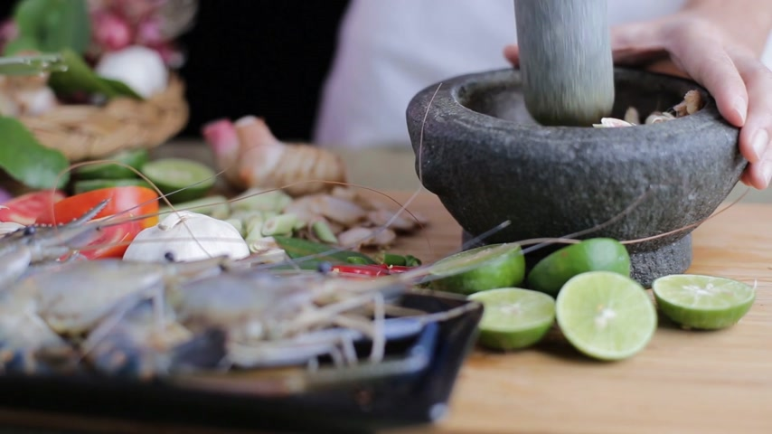 soğancık : Female hand pounding Thai herb in the mortar to make Tom Yum Kung with all spices and prawns beside on the chopping board.