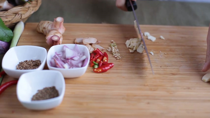 Female hand crush garlics and slice them with chef knife on bamboo wooden chopping block with other Thai herbs beside for making Thai red curry or Panang recipe.